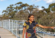 Teenage Girl On Overpass Walkway Wearing Aboriginal Design Shirt