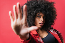 Scared Black Woman Showing Stop Sign On Red Background