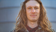 Full Face Of Young Bloke With Long Hair And Facial Piercings