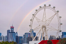 A Rainbow Arching Over A Large Ferris Wheel And A City Skyline