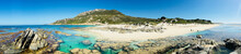 Panorama Of Remote Idyllic Beach With Clear Water, Rocks And Small Figures On Beach