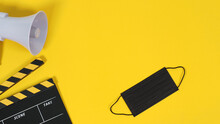 Clapperboard Or Movie Slate And Black Face Mask And Megaphone On Yellow Background. Yellow And Black Color.