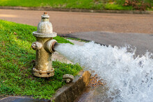 Open Fire Hydrant Gushing Water Onto Street.