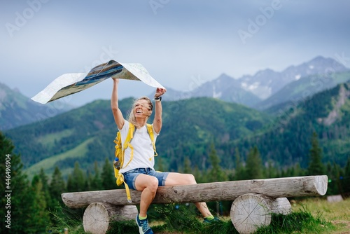 Fotografie, Obraz A girl traveler with a yellow backpack sits on a bench with a paper map