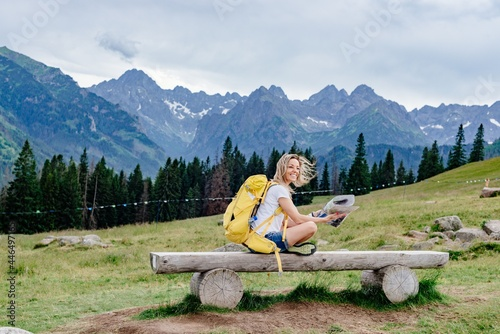 Fotografie, Obraz Smiling woman traveler with a yellow backpack sits on a bench with a paper map