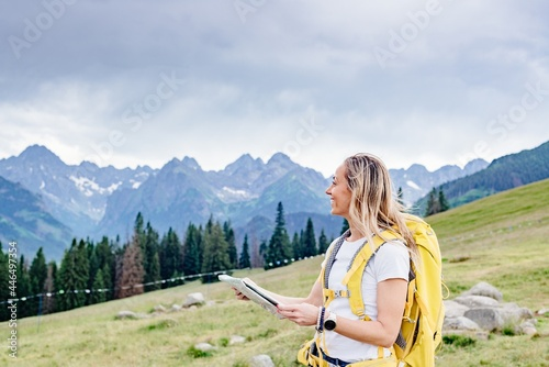 Obraz na plátně Smiling girl traveler with yellow backpack and paper map in the mountains