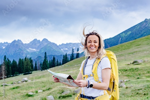 Fotografie, Obraz Smiling blonde female hiker with map in the mountains