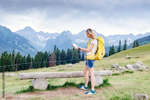 Obraz na plátně Adventurous blonde woman navigating with a topographic map in beautiful mountains