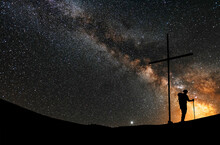 Starry Night, Silhouette Of The Hiker With Backpack And Stick, Stands On The Hill Near The Cross. Behind Him Bright Milky Way Galaxy. Space Astronomical Background.