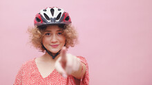 Beautiful Young Girl Wearing A Bicycle Helmet Smiling And Pointing At The Camera. The Girl Is Dressed In A Casual Pink Top. Cycling For Leisure Healthy Lifestyle Concept. Isolated Over Pink Background