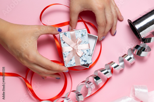 Photo Close-up of a hand holding a small gift box with a bow on a solid pink backgroun