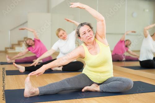 Fototapeta premium Mature European women are doing head-to-knee forward bend