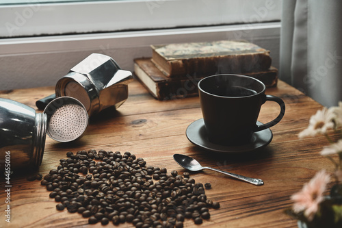 Foto Roasted coffee beans, coffee cup and coffee maker moka pot on wooden table