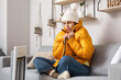 Young woman sitting near electric heater at home. Concept of heating season