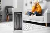 Young woman sitting in room with electric heater. Concept of heating season