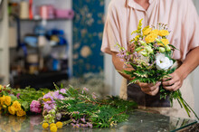 Crop Woman Arranging Flowers In Bouquet In Floral Shop