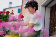 Cheerful Gardener Watering Blooming Flowers On Terrace