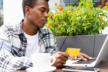 Black Man Making Payment With Plastic Card During Online Shopping