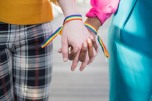 Crop Multiracial Lesbian Couple With Rainbow Bracelets Holding Hands