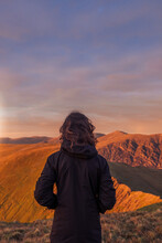 Unrecognizable Traveler Admiring View Of Mountains At Sunset