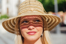 Woman In Straw Hat On Sunny Day In City
