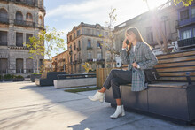 Trendy Young Woman Talking On Phone On Urban Street
