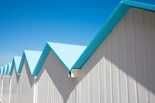 Diagonal Row Of White Beach Cabins In Albisola, Liguria, Italy. Blue Sky On The Background.
