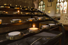 Votive Candles Lit As Prayers For Loved Ones Inside A Christian Church