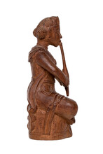 Closeup Of An Antique Carved Wooden Figure Of An Asian Man Sitting And Playing A Musical Instrument. A Carved Sculpture Isolated On A White Background. Macro.