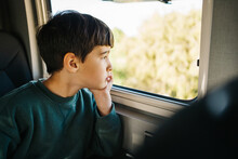 Little Boy Looking Out The Window Of A Motorhome