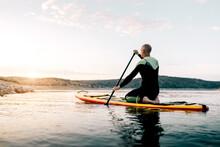 Man On Paddle Board Floating On Lake