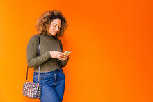 Afro Woman Using Mobile With An Orange Wall