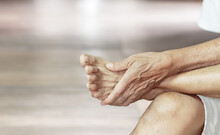 Close-up Of A Man's Arm Holding A Painful Foot Caused By Vaccination. Neurological Concept, Numb Hands And Feet