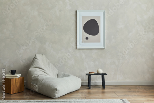 Stylish composition of minimalistic living room interior with mock up poster frame, grey pouf, black tiny coffee table, wooden cube and elegant personal accessories on it. Template.