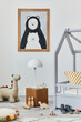 Stylish scandinavian child's room interior with mock up poster frame, creative bed, wooden cube, lamp, plush and wooden toys and hanging textile decorations. Grey walls, carpet on the floor. Template.
