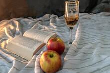 Nature Morte Avec Lumière Douce, Livre, Verre En Cristal Avec Alcool  Et Deux Pommes
