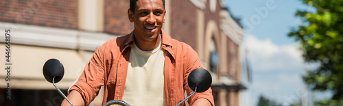 Fotografia, Obraz young african american man looking away while riding scooter outdoors, banner
