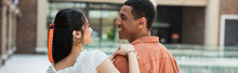 Young Interracial Couple Smiling At Each Other Outdoors, Banner