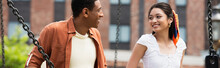 Young And Happy Interracial Couple Smiling At Each Other Outdoors, Banner