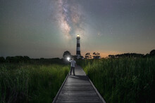 A Man Walking On A Pathway Towards Bodie Island Lighthouse And The Milky Way Galaxy