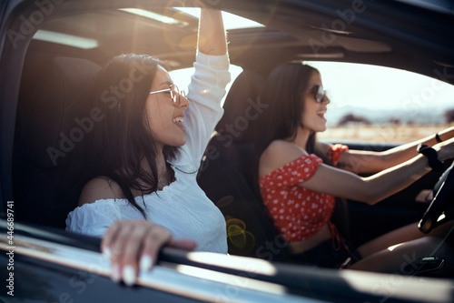 Tablou Canvas Pretty young women singing while driving a car on road trip on beautiful summer day