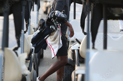 Photo A golfer carries his clubs just prior to placing them on a golf cart
