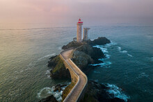Aerial View Of A Bridge Across The Ocean Leading To A Red Lighthouse Called Phare Du Petit Minou, Bretagne, France.