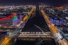 Aerial View Of Samuel Beckett Bridge Crossing The Liffey River At Night With City Skyline In Background, Dublin, Ireland.