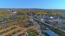 An Aerial View Of An Amish Mud Sale With Buggies, Farm Equipment And Other Crafts In Early Spring