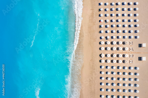 Valokuva Top view of a beach with symmetrical sunbeds and parasols next to turquoise sea