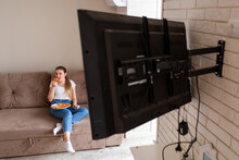 Beautiful Woman Eating Pizza And Watching TV Holding Remote Cont
