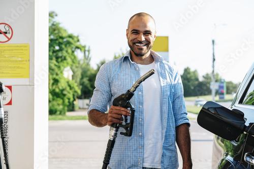 Canvastavla Man filling gasoline fuel in car at gas station