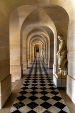 An Arched Ceiling And A Checkered Floor Provide Symmetry And Perspective In A Hallway At The Palace Of Versailles In France.