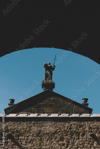 Fotomural Vertical shot of the backside of a statue with a sword in Toledo, Spain on a bri